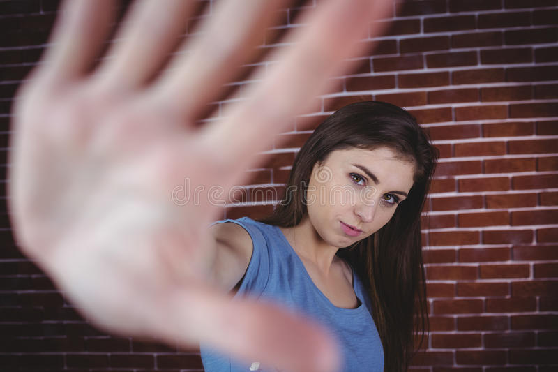 Pretty brunette with hand up stock photos