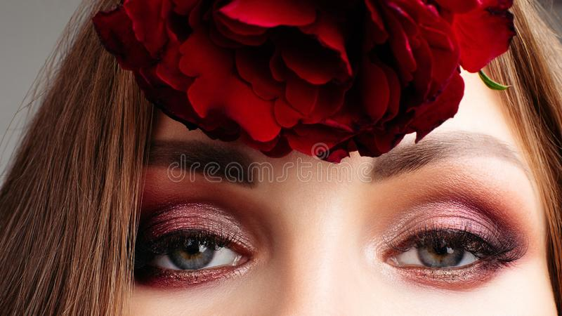 Pretty brunette lady with bright make up holding roses. royalty free stock images