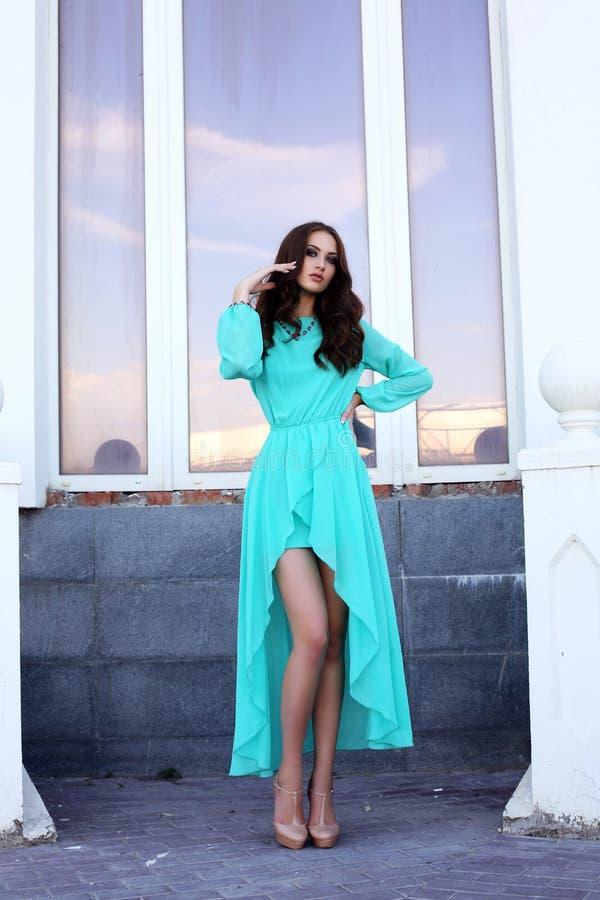 Pretty brunette in luxurious blue dress posing beside a window. Fashion outdoor photo of beautiful sensual woman in luxurious blue dress stock photography