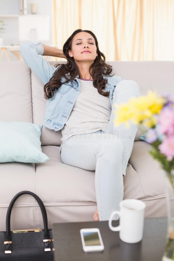Pretty brunette relaxing on the couch. At home in the living room royalty free stock images
