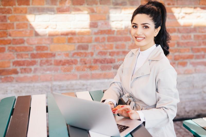 Pretty brunette student female wearing elegant white coat working at computer writing her thesis looking with smile at camera. Bu stock images