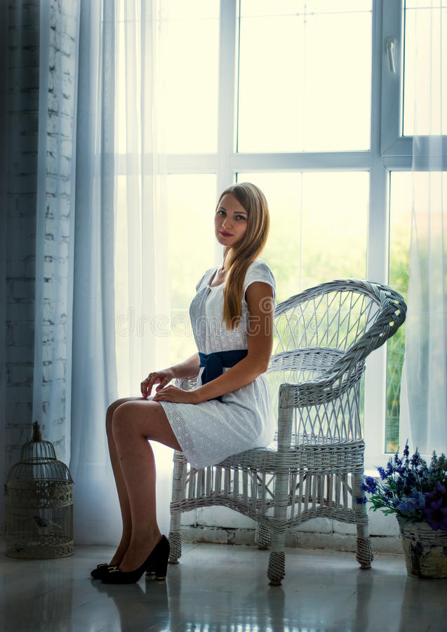 Pretty brunette wearing white dress posing on the couch stock images