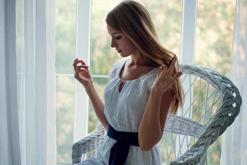 Pretty brunette wearing white dress posing on the couch stock image