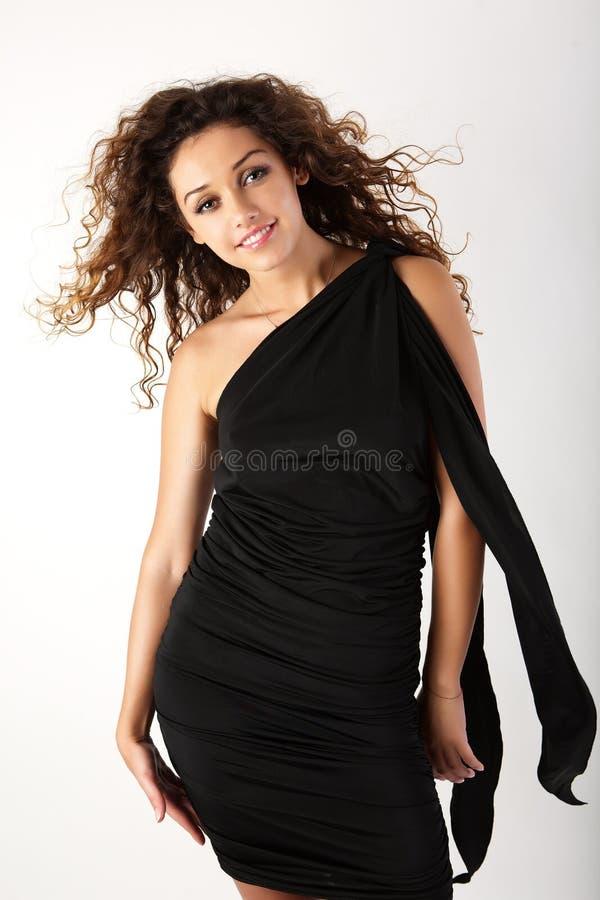 Pretty brunette woman in the black dress. stock photo
