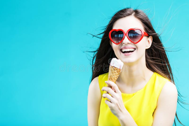 Girl with Icecream. Pretty brunette woman dressed in yellow shirt and sunglasses eating waffle icecream before blue background royalty free stock images