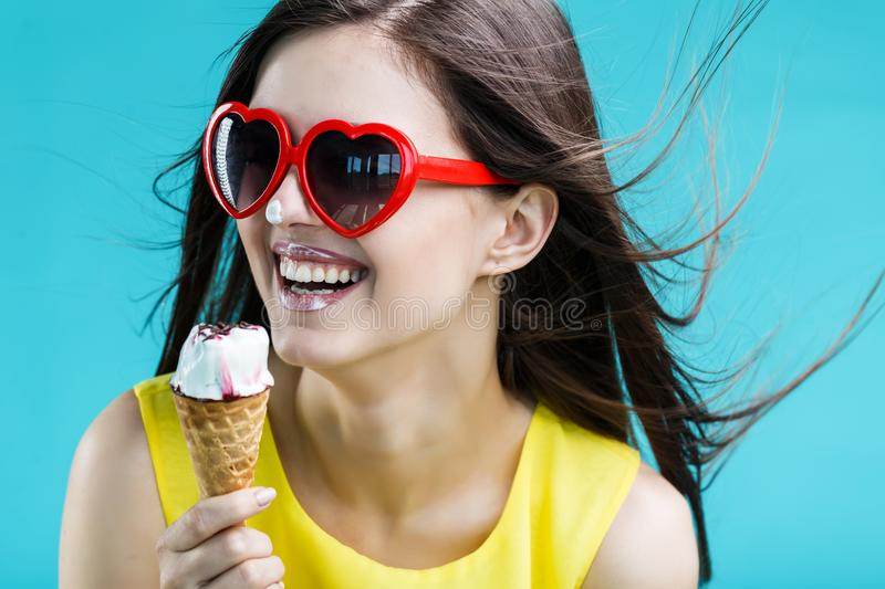 Girl with Icecream. Pretty brunette woman dressed in yellow shirt and sunglasses eating waffle icecream before blue background royalty free stock photo