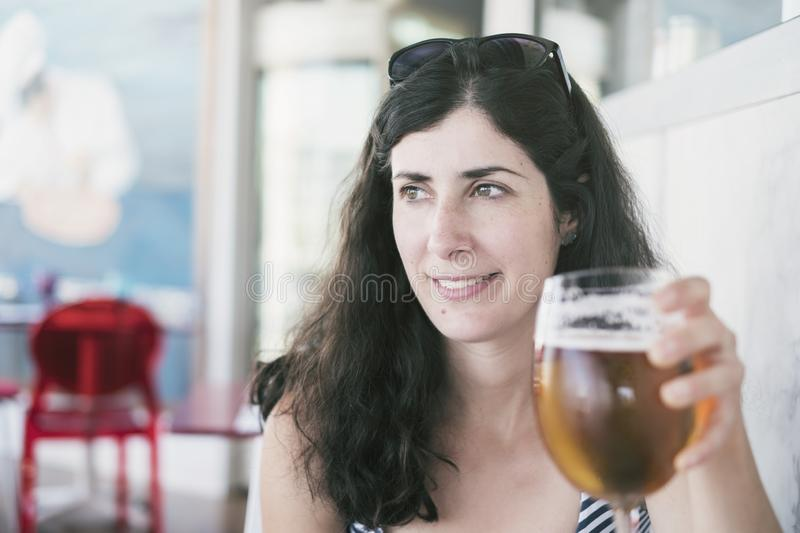Beauty woman drinking a cup of beer in restaurant royalty free stock photography