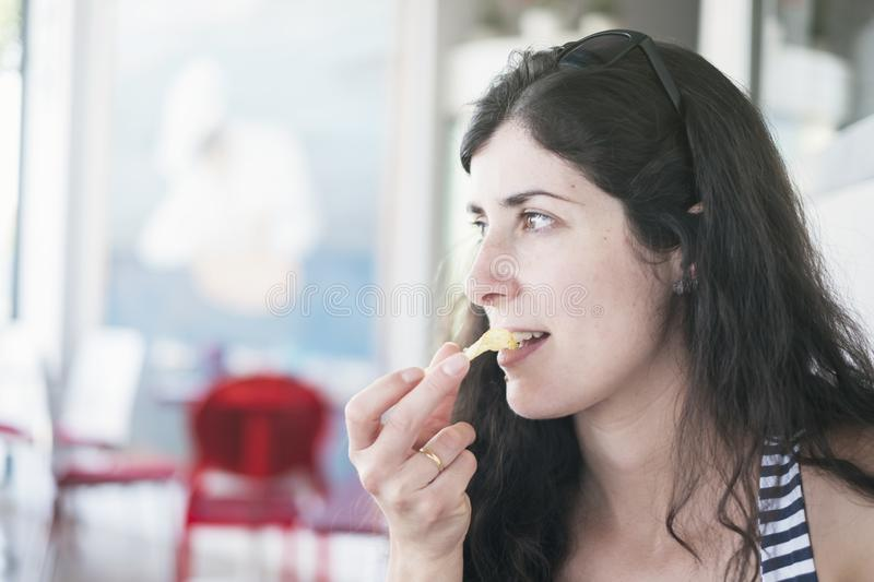 Pretty brunette woman eating chips in restaurant stock photos