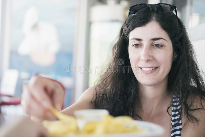 Pretty brunette woman eating chips in restaurant stock photography