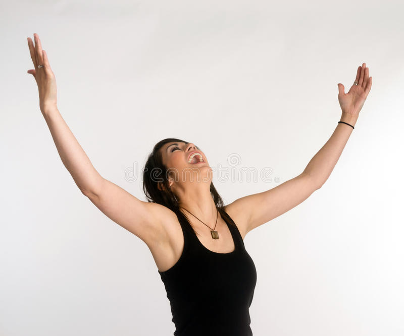 Pretty Brunette Woman Holds Arms Outstretched Jubilant Looking Up royalty free stock images