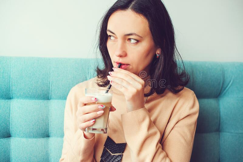 Pretty brunette woman holds glass of hot latte. Girl enjoys coffee drink during break stock photo