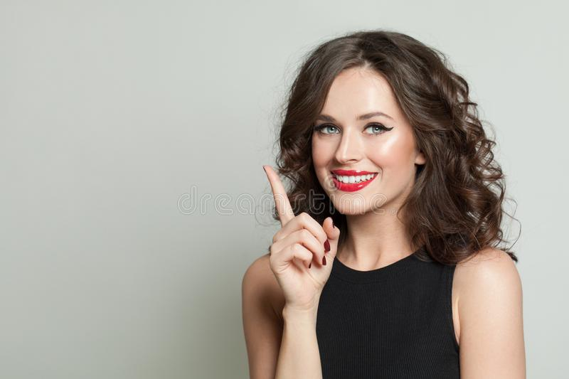 Pretty brunette woman pointing up and smiling royalty free stock images