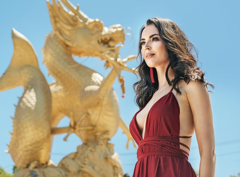 Pretty brunette lady posing with a golden dragon in the background stock photo