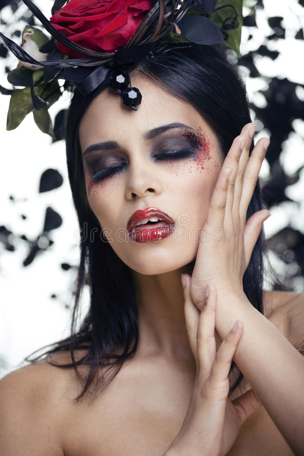 Pretty brunette woman with rose jewelry, black and red, bright make up a vampire