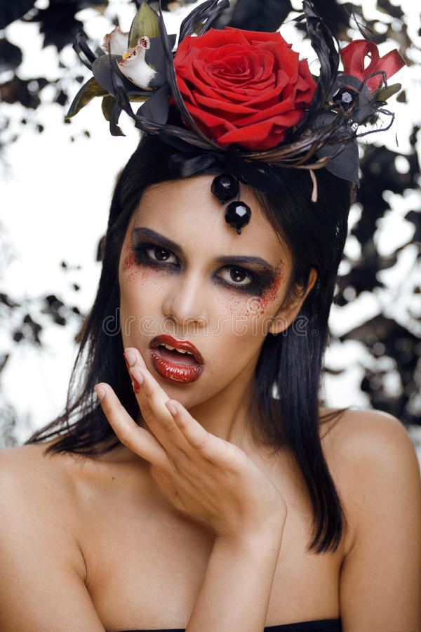 Pretty Brunette Woman With Rose Jewelry, Black And Red, Bright Make Up A Vampire Stock Images
