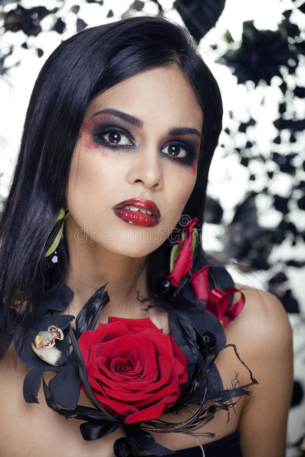 Pretty brunette woman with rose jewelry, black and red, bright make up a vampire closeup red lips. Halloween concept royalty free stock photos
