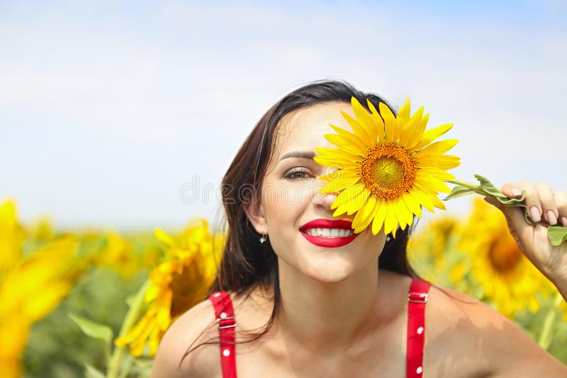 Pretty brunette woman in sunflower field royalty free stock images