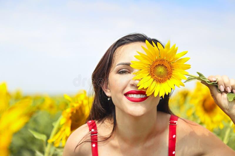 Pretty brunette woman in sunflower field. Pretty brunette woman wearing red polka dots dress in sunflower field royalty free stock images