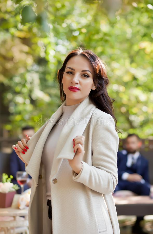 Pretty brunette woman in a white coat standing in outdoor cafe. Well-dressed man in the background stock photos