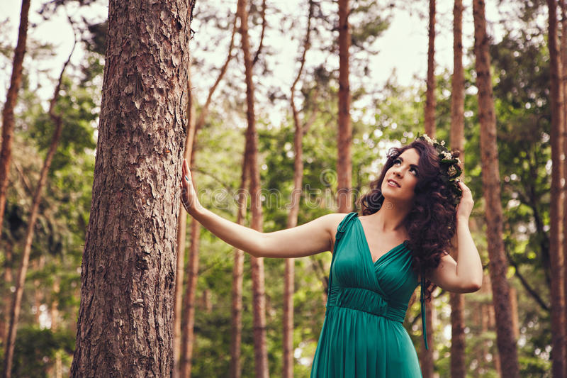 Pretty brunette with wreath in the forest looking up royalty free stock photography
