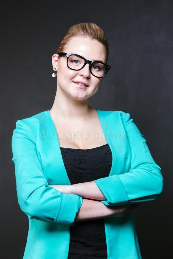 Pretty business blonde woman in glasses and jacket poses royalty free stock images