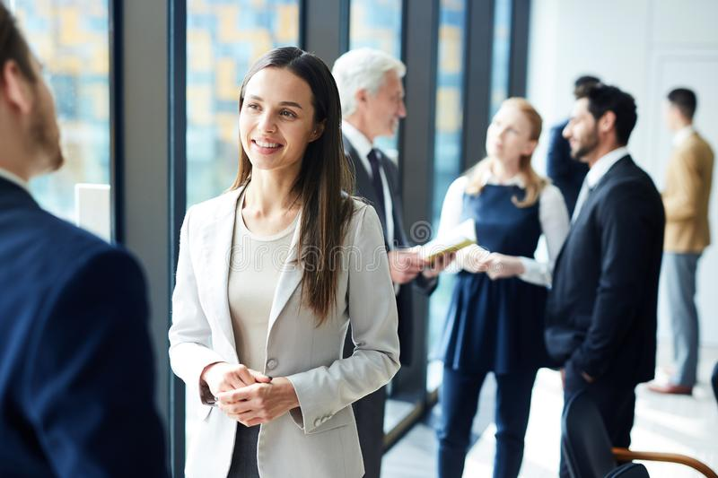 Pretty business lady talking to colleague. Smiling pretty young business lady in jacket talking to colleague and discussing business forum topics during break stock images