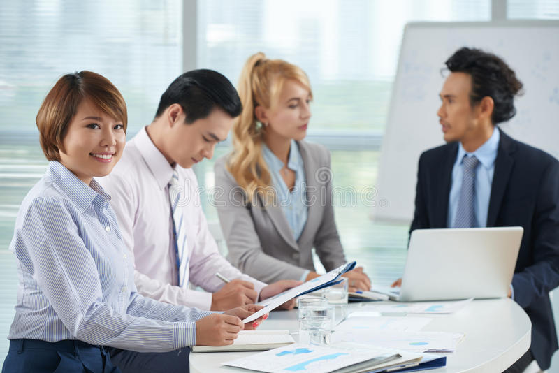 Pretty business lady. Young Asian business lady at meeting with her colleague royalty free stock image