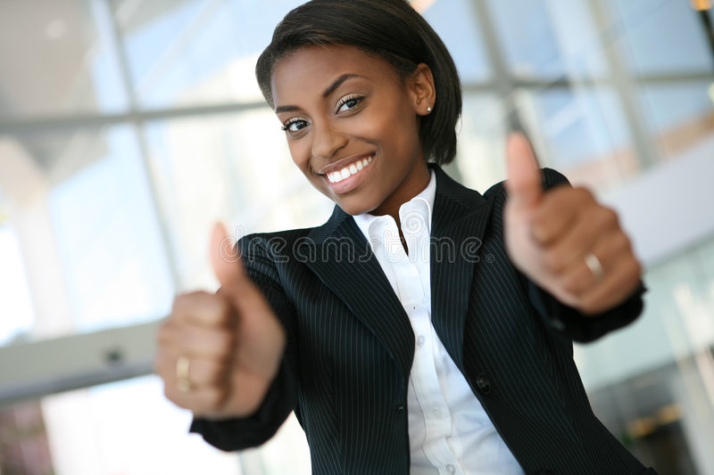 Pretty Business Woman. A pretty african american business woman with thumbs up royalty free stock photos