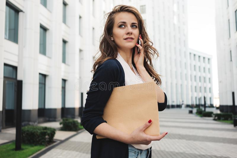 Pretty business woman hold paper documents and discuss financial news on smartphone stand among urban space. Young female lawyer holding folder and looking stock image