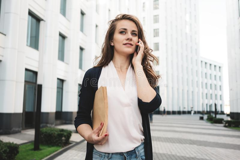 Pretty business woman hold paper documents and discuss financial news on smartphone stand among urban space. Young female lawyer holding folder and looking stock images