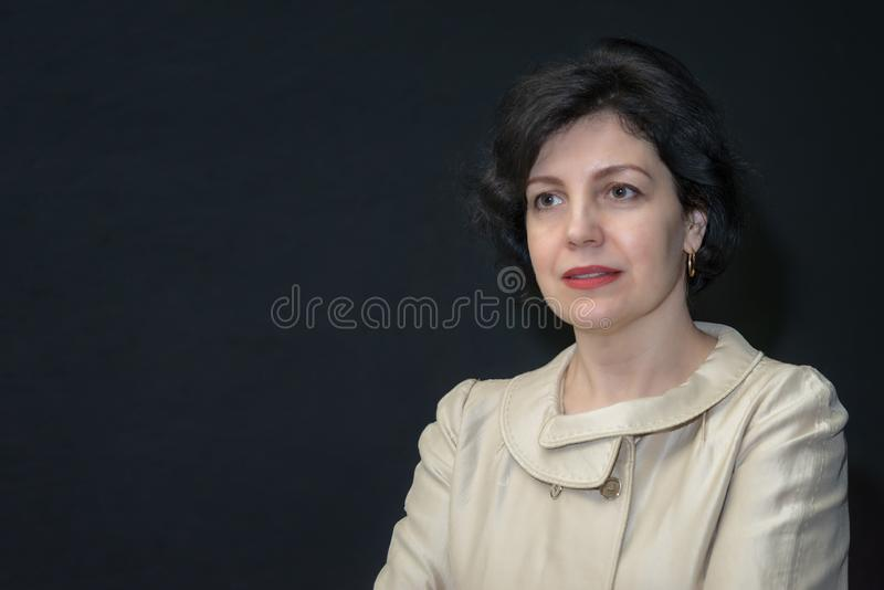 Attractive middle aged woman in business suit against black wall royalty free stock images