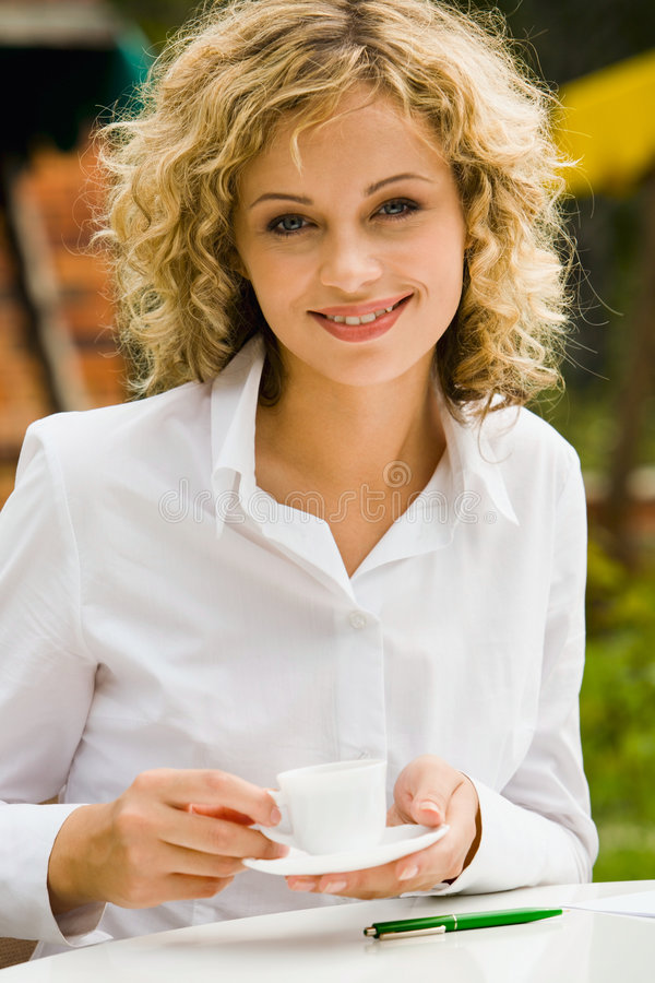 Pretty businesswoman. Pretty smiling businesswoman with the cup of coffee outdoor stock images