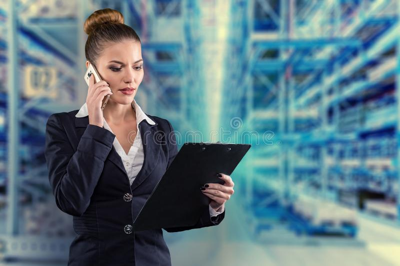 Pretty businesswoman with clipboard talks on phone with warehouse background stock photo