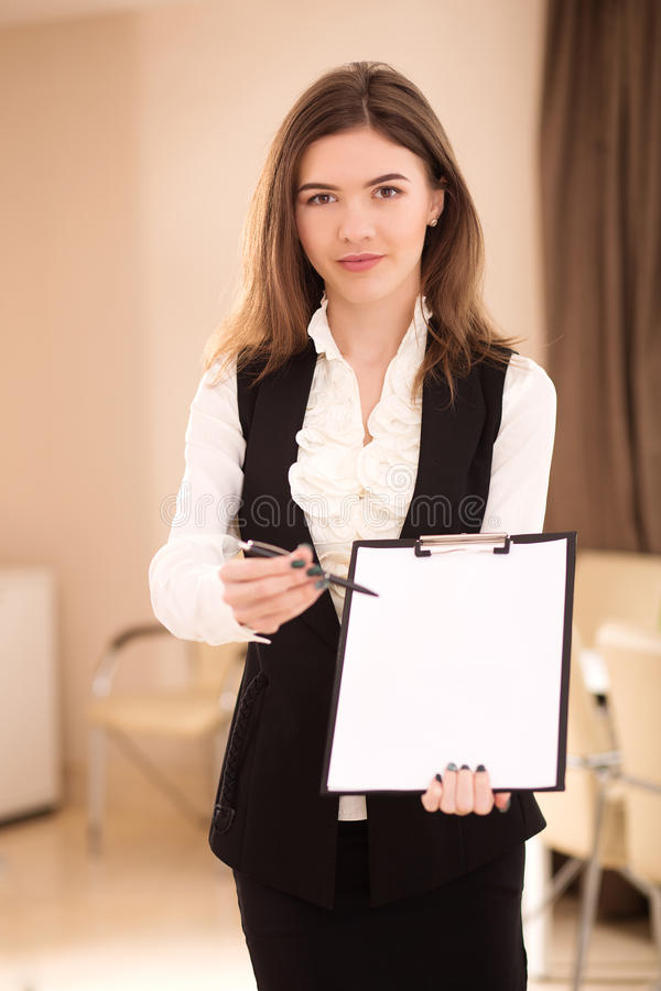 Pretty businesswoman offering to sign a contract stock photography