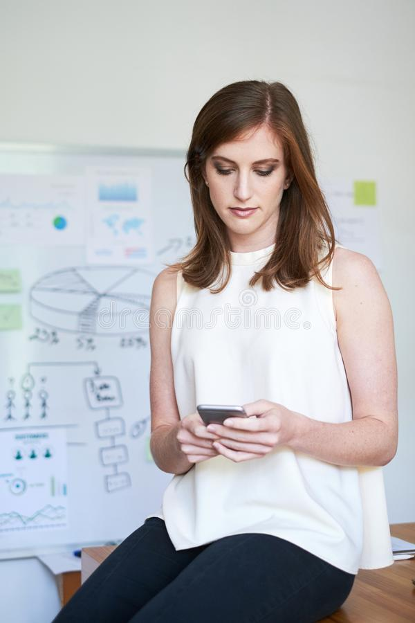 Pretty businesswoman with smartphone in office stock photos