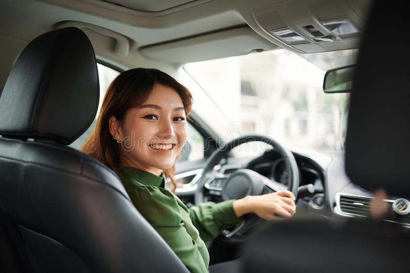 Pretty businesswoman smiling and driving in her car stock photo