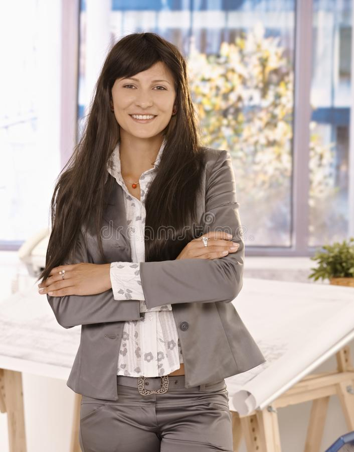 Pretty businesswoman standing in office. Pretty businesswoman with long hair standing in office with arms crossed, looking at camera, smiling royalty free stock photos