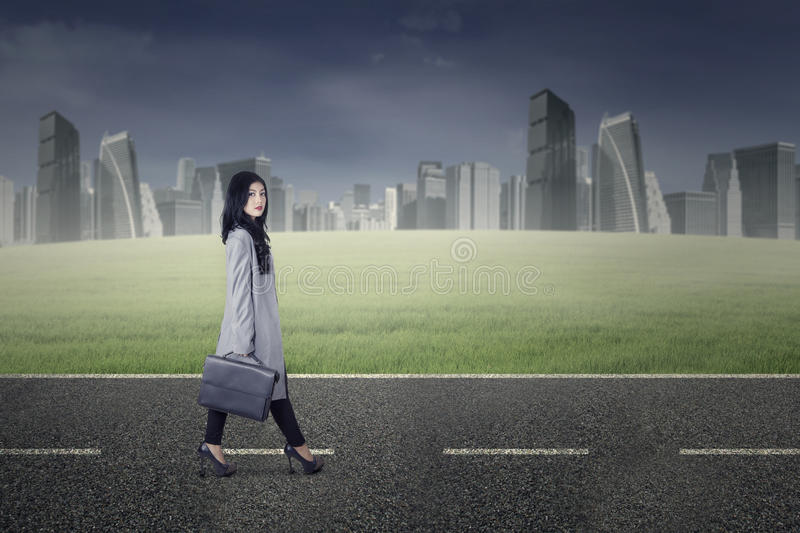 Pretty businesswoman walking on the road stock image