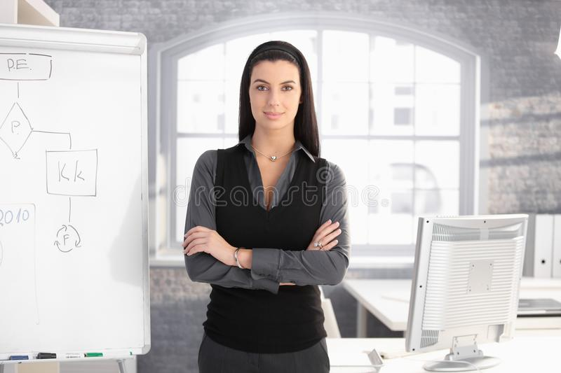 Pretty businesswoman at whiteboard. Pretty businesswoman standing at whiteboard in office with arms folded, smiling stock images