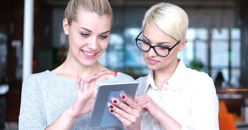 Pretty Businesswomen Using Tablet In Office Building during conference royalty free stock photos