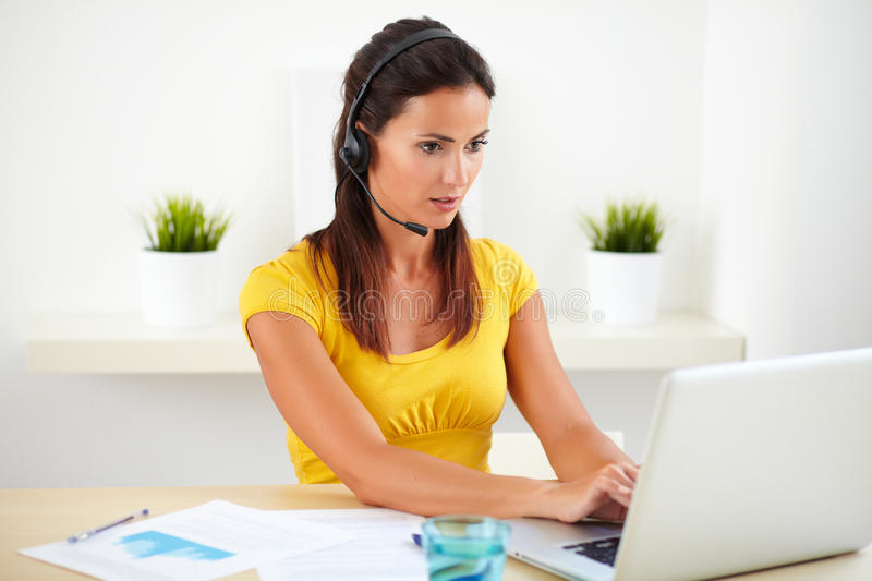 Pretty callcenter worker conversing by earphone. While sitting in her workplace royalty free stock photo