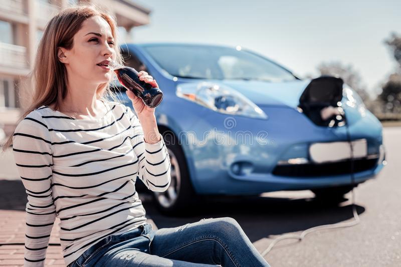 Pretty calm woman sitting and drinking cola. stock images