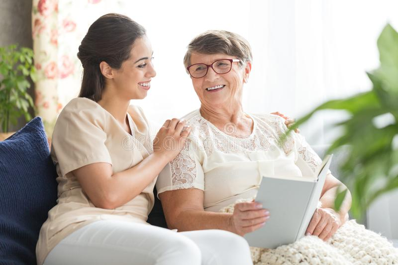 Pretty caregiver and elderly woman. Pretty caregiver sitting with happy elderly women in glasses who is reading book royalty free stock photos