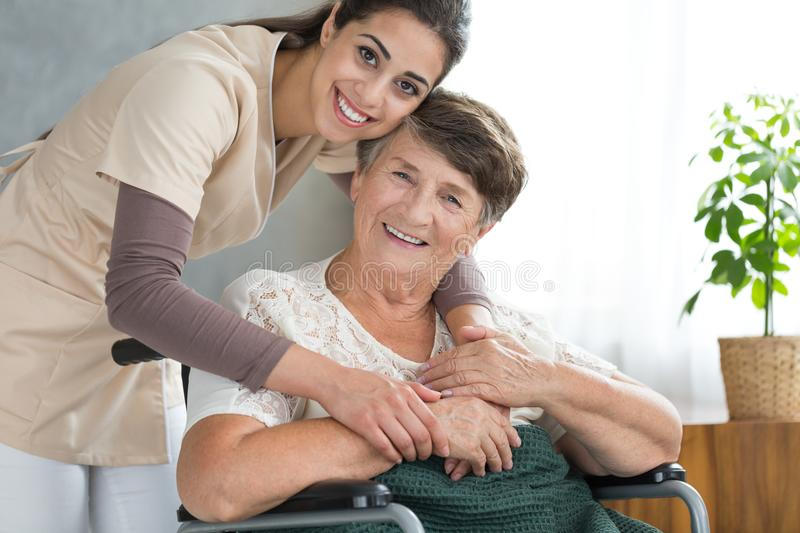 Pretty caregiver hugging disabled senior. Pretty caregiver in uniform hugging disabled senior women during visit at home stock photos