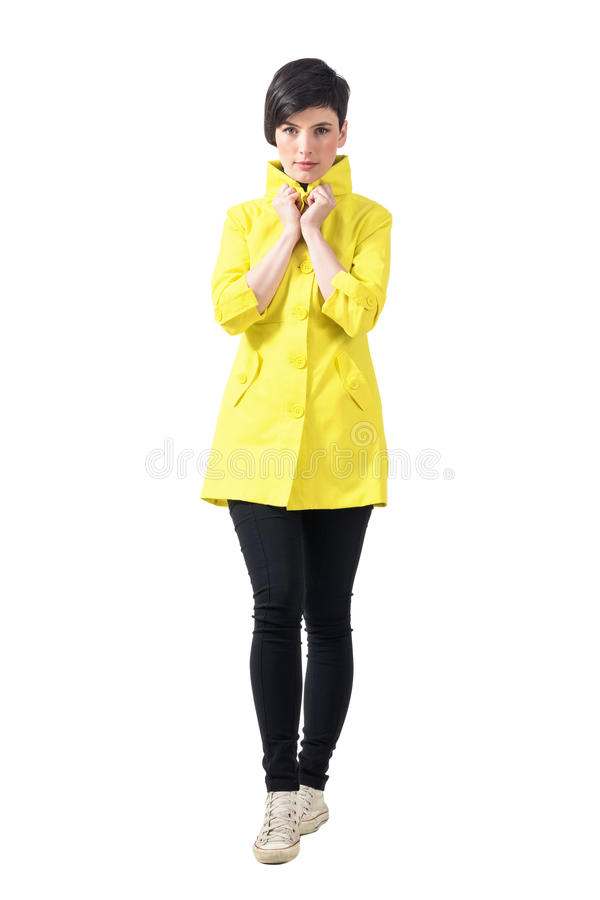 Pretty catwalk female model in yellow coat walking towards camera holding collar stock images
