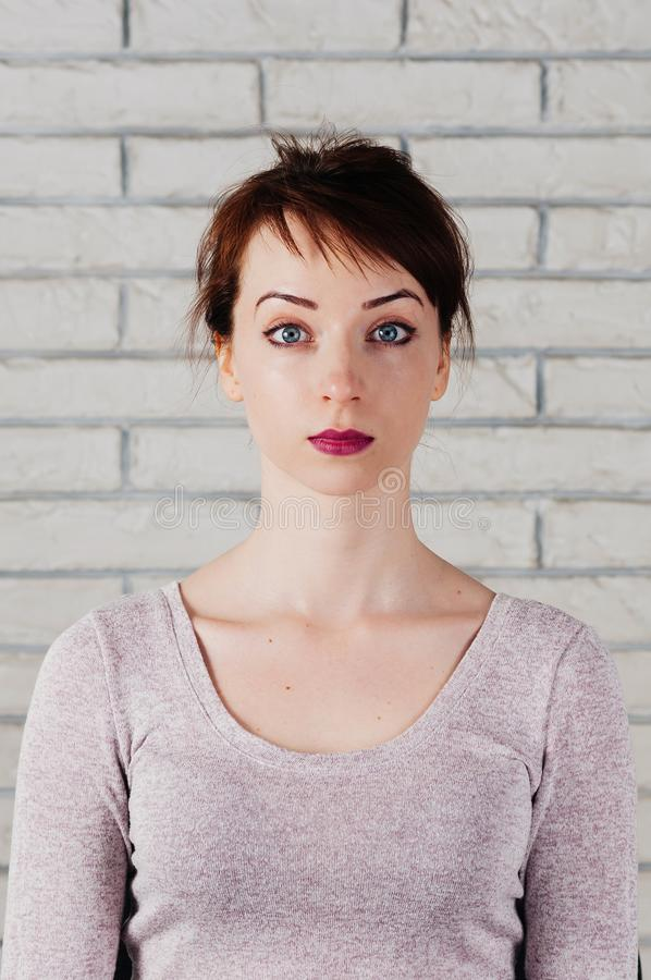 A pretty caucasian girl with surprised face. A pretty girl with surprised face, big blue eyes, brows up, with white brick wall in the background. Face mimic royalty free stock photography