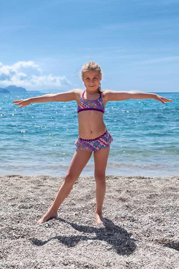Pretty Caucasian girl in swim suit standing on seashore with arms stretching lateral. Full lenght royalty free stock image