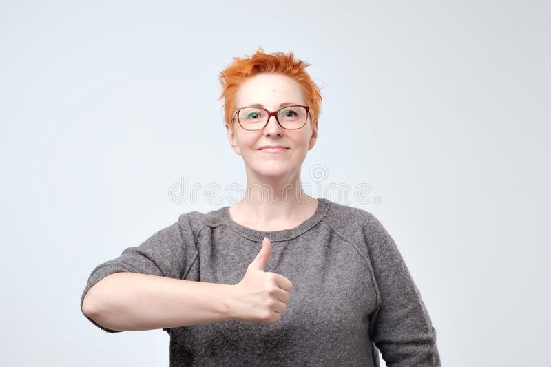 Pretty caucasian mature woman with red hair showing thumbs up isolated over a white background royalty free stock photography