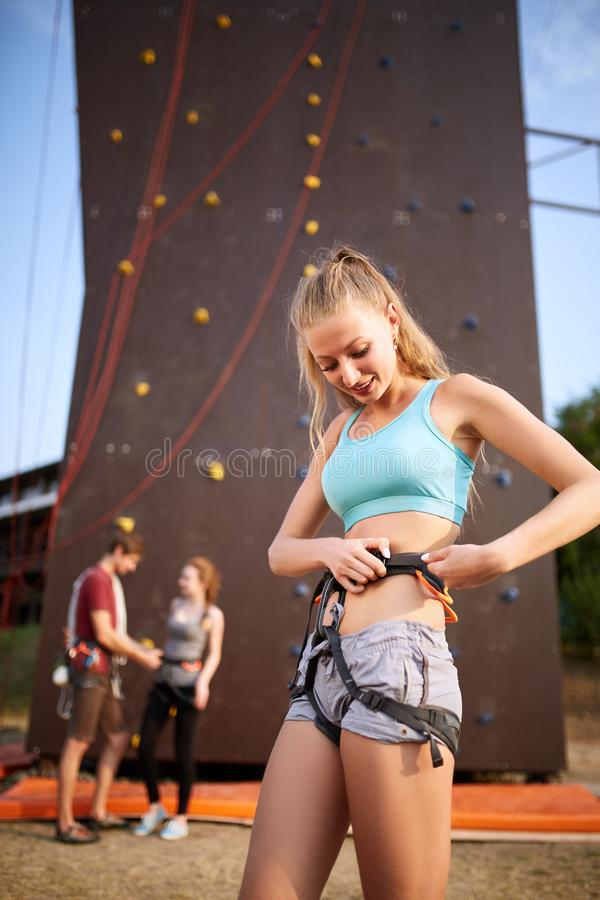 Pretty caucasian woman puts on belaying harness for practice on artificial rock wall outdoors. Slim strong healthy royalty free stock photography