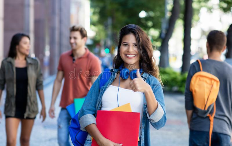 Pretty caucasian young adult woman walking in city with group of students royalty free stock photo